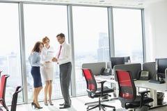 Full längd av businesspeople som i regeringsställning diskuterar Arkivbilder