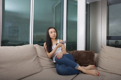 Full längd av hållande ögonen på TV för ung kvinna i vardagsrum Royaltyfri Bild