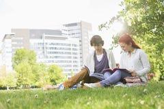 Full längd av unga manliga och kvinnliga vänner som studerar på högskolauniversitetsområdet Arkivfoton