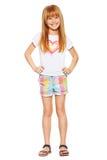 Full längd en gladlynt liten flicka med rött hår i kortslutningar och en T-tröja; isolerat på viten Arkivbild