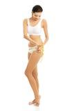Full längdkvinna som mäter hennes höfter Royaltyfri Foto