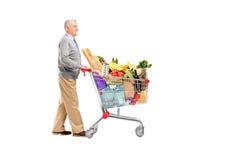 Full längdpotrait av en gentleman som mycket skjuter en shoppingvagn Royaltyfri Bild