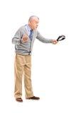 Full längdstående av en ilsken mogen man som rymmer ett bälte och en t Arkivfoton