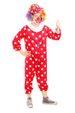 Full längdstående av en le lycklig clown i röd dräktgiv Royaltyfri Bild