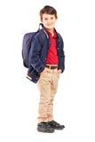 Full längdstående av en skolapojke med ryggsäckanseende Arkivbild
