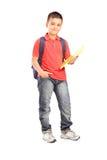 Full längdstående av en skolpojke med ryggsäcken som rymmer en anteckningsbok Arkivbilder