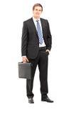 Full längdstående av en ung affärsman i dräkten som rymmer en su Arkivbilder