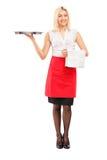 Full längdstående av ett le kvinnligt servitrisinnehav ett magasin Arkivfoto