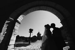 Full of love stylish groom with luxury blonde bride on the background the old castle stock photo