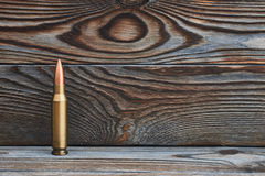 Full metal jacket bullet. On wooden background with copy space Royalty Free Stock Photos