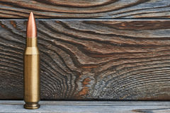 Full metal jacket bullet. On wooden background with copy space Stock Images