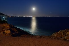 A Full Moon Above the California Coastline. A full moon shines above the city of Santa Monica in the far distance, as seen from Malibu down the California Royalty Free Stock Photo