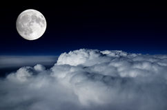 Full moon above cloud deck. Full moon lighting up the clouds below Royalty Free Stock Photo