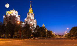 Full Moon above glowing main buildings of the Moscow State University campus stock images