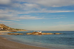 Full moon on beach of Palmilla. With a bird colony on the rocks royalty free stock photography