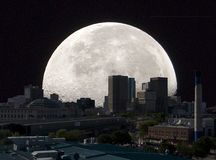 Full moon cityscape. A moon rising over a cityscape stock image