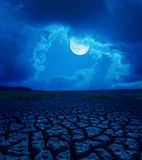 Full moon in clouds over desert Stock Photography