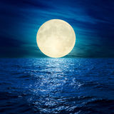 Full moon in clouds over water Royalty Free Stock Photos
