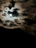 Full moon clouds sky. A full moon glowing in a night sky with clouds Royalty Free Stock Images