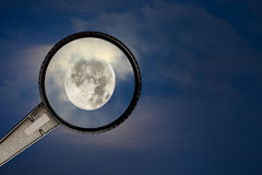 Full moon and cloudy sky with magnifying glass Royalty Free Stock Image