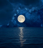 Full moon in dark clouds over sea Stock Photography