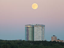 Full moon in evening sky over urban houses Royalty Free Stock Images