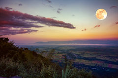 The full moon in the evening after sunset. Outdoors at nighttime. The full moon in the evening after sunset. Scenes from view point with colorful sky. Beautiful royalty free stock photography