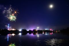 Full Moon and Fireworks at the Isle of Wight Festival 2108. Fireworks, lights and a near full `strawberry` moon reflect off the River Medina on the last night of Royalty Free Stock Images