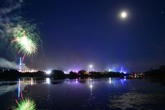 Full Moon, Fireworks and Reflections at the Isle of Wight Festival 2018. Fireworks, lights and a near full `strawberry` moon reflect off the River Medina on the Royalty Free Stock Photo