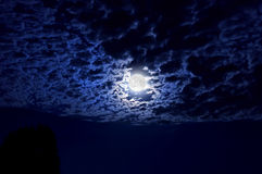Full moon glowing in night sky illuminating cloud cover. Full moon with indigo hues glowing in night sky illuminating clouds in wide angle perspective royalty free stock photography