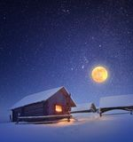 Full moon and hut. Winter landscape with a starry sky and the full moon. The light in the cabin in the mountains Stock Images