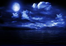 Full moon image with water. The full moon in the night sky reflected in water Royalty Free Stock Image