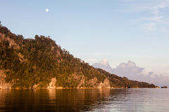 Full Moon and Morning Light on Limestone Island in Raja Ampat Royalty Free Stock Photography