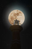 Full moon at night with lighthouse on clear sky with stars Stock Photos