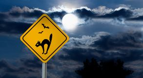 Full Moon in the Night Sky and Halloween Road Sign - Cat, Bats. Dark Cloudy Sky with Full Moon and the road Sign Yellow Square `Caution, Halloween` is a black Stock Photography