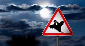 Full Moon in the Night Sky and Halloween Road Sign. Dark Cloudy Sky with Full Moon and the road Sign white Triangle with a Red Border `Caution, Halloween` is a Stock Photos
