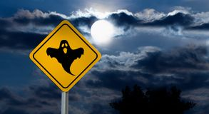 Full Moon in the Night Sky and Halloween Road Sign - Ghost. Dark Cloudy Sky with Full Moon and the road Sign Yellow Square `Caution, Halloween` is a black Royalty Free Stock Image