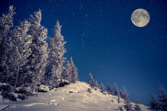 Full moon in the night sky in winter mountains royalty free stock image