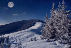Full moon in night sky in winter mountains Royalty Free Stock Images