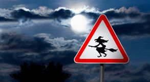 Full Moon in the Night Sky and Witch Road Sign. Dark Cloudy Sky with Full Moon and the road Sign white Triangle with a Red Border `Caution, Halloween` is a black Royalty Free Stock Images