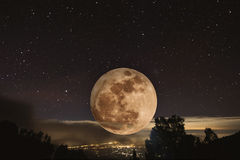 Full moon at night with stars, with lights from city view from highland mountain Royalty Free Stock Image