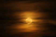 Full Moon in Orange Clouds. A full moon rises throgh the orange clouds of evening in Uganda, Africa Royalty Free Stock Images