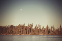 Full moon over alpine mountain lake Stock Photo