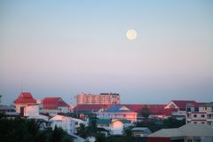 Full moon over the apartment buildings during early morning Stock Image