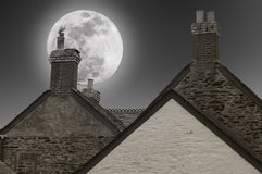 Full moon over the chimneys Stock Photos