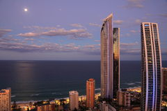 Oceanfront living by full moon scenery. Clear views over the ocean from Surfers Paradise, Gold Coast, Australia, by full moon and a cloudy sky at the blue hour stock image