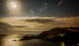 Full moon over coastal view. Full moon shines over calm sea and coastal mountain village Stock Photo
