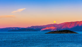 Full moon over Crete at sunset Stock Photos
