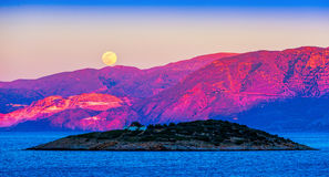 Full moon over Crete at sunset Stock Image