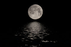 Full moon over dark black sky at night. Full moon reflected water over dark black sky at night Royalty Free Stock Photos